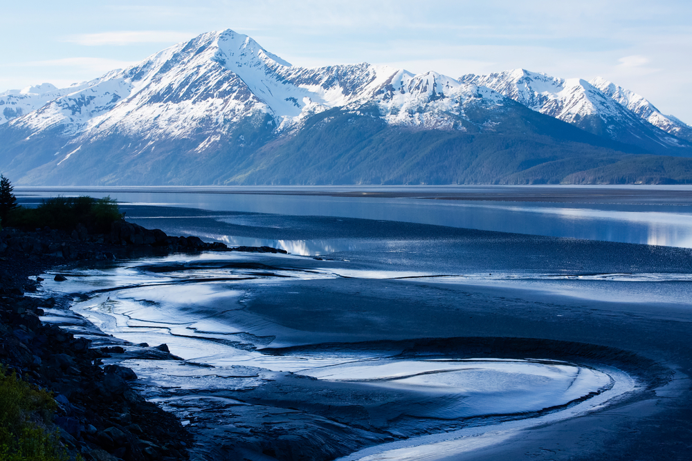 Vast body of water in foreground with snow-capped mountains in background.