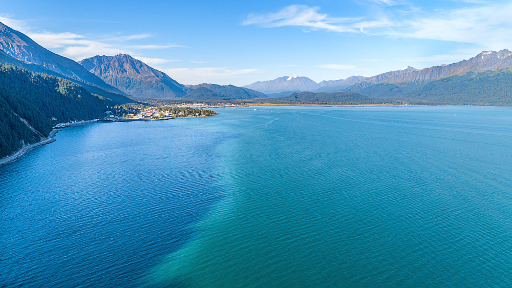 Areial view of bright blue water with town and mountains in background.