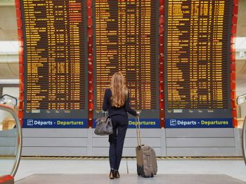 Female with blonde hair looks over flight information screen while holding onto her carry-on suitcase and matching gray bag.