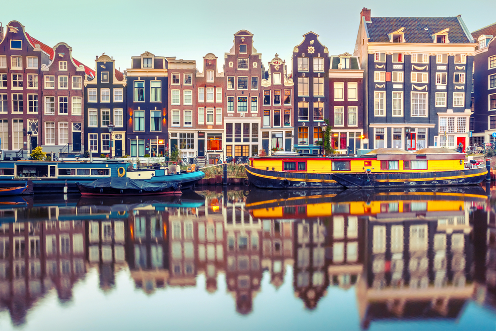 traveling to amsterdam will reveal beautiful canals and buildings