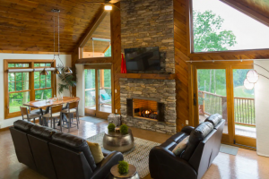 cabin with towering glass windows, stone fireplace, and cozy sitting area