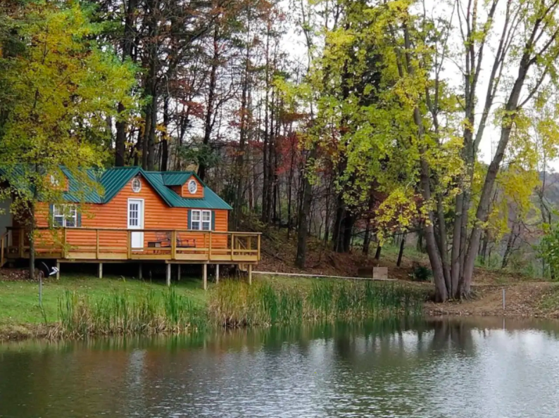 cute orange cabin sitting on lake