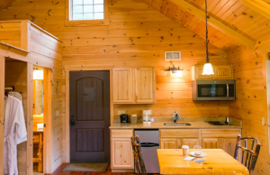 light wood kitchen with dark paneled door and dining table for two cabins in Ohio