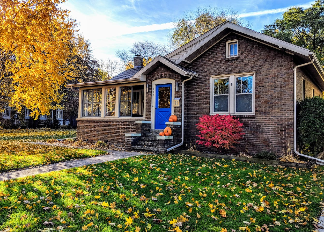 Modern 1920s Bungalow decorated with autumn foliage and pumpkins
