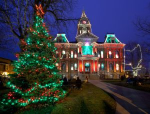 tall lit Christmas tree in front of historic building