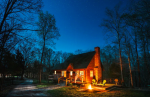 log cabin with brick chimney at night Airbnbs in Kentucky