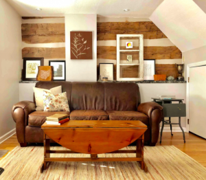 brown couch with log cabin-style wall behind it best Airbnbs in Columbus
