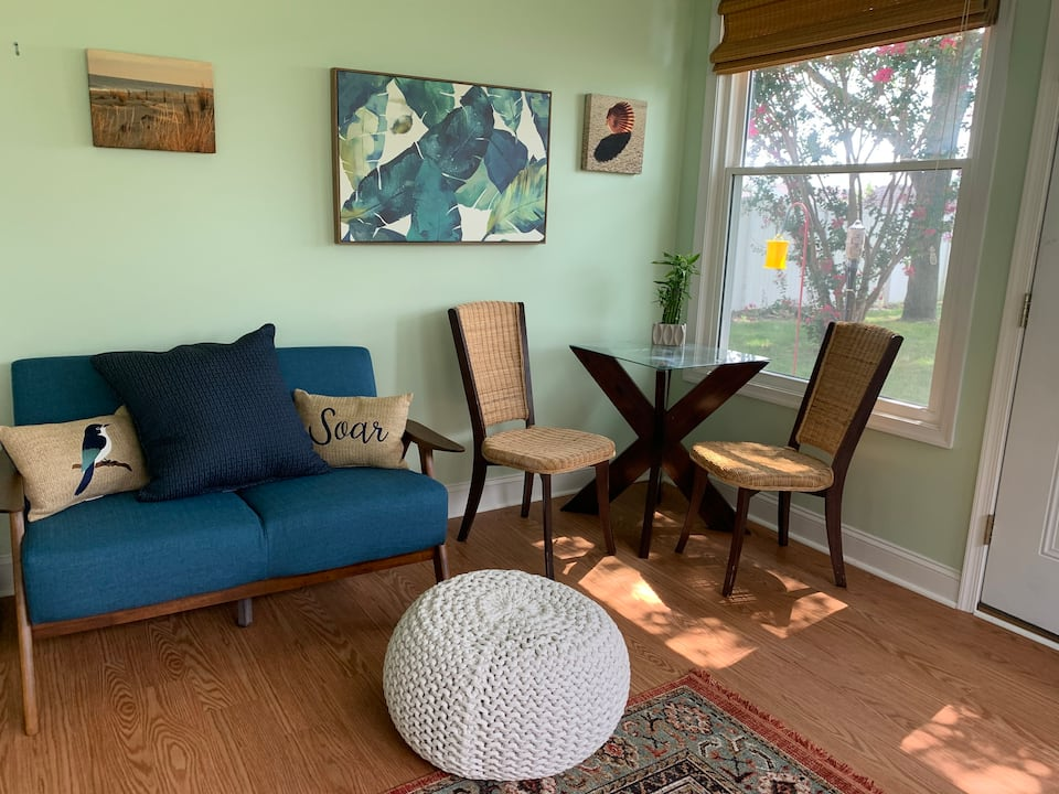 Photo of light-filled front room with table and chairs, blue couch and bright painting on the wall.