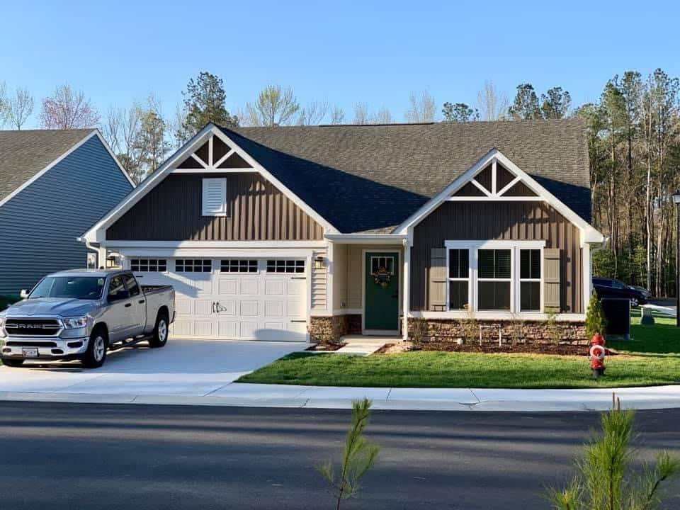 Beautiful house with brown siding and white trim with truck in parking lot.
