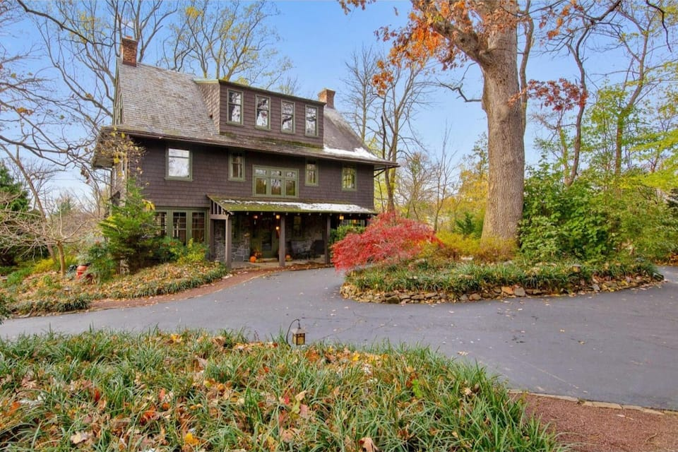 Large craftsman-styled house on wooded lot with leaves changing for autumn. Large circular driveway in front of house.
