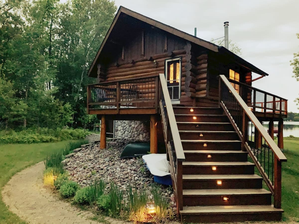 Charming log cabin with lighted steps leading up to wrap around decking.