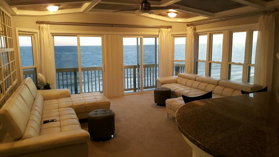 Lovely room with beige couches and a lot of windows looking out onto the ocean.