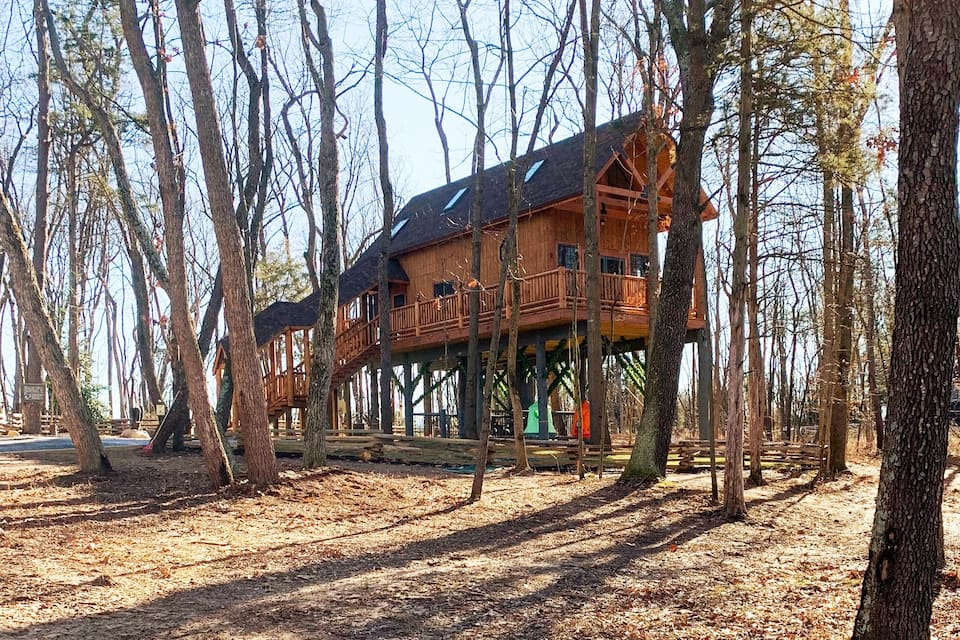 Tree house cabin in Virginia with wooden railing and surrounded by trees