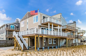 light brown beach house with American flag