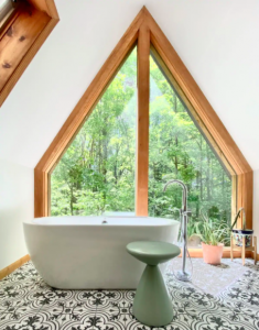 interior of A-frame cabin with floor to ceiling windows and deep bath tub