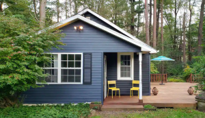 dark blue exterior of cabin with bright yellow chairs on front porch