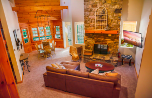 living room area of cabin with stone fireplace