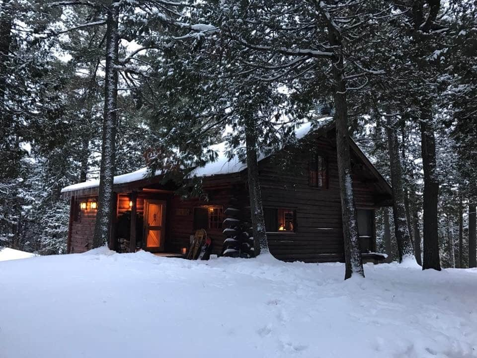 Picture of log cabin in the woods with snowfall around it, on the rooftop and in the trees.