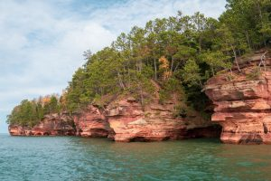 red rocks with green trees on blue water