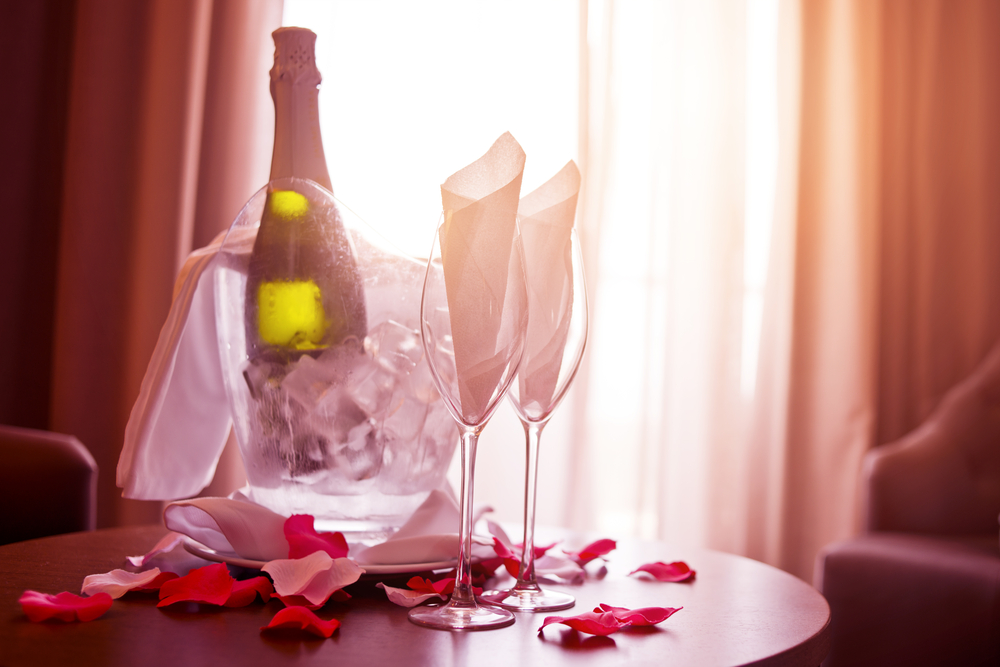 Photo of charming hotel scene with champagne and roses on a table with sunlight streaming in