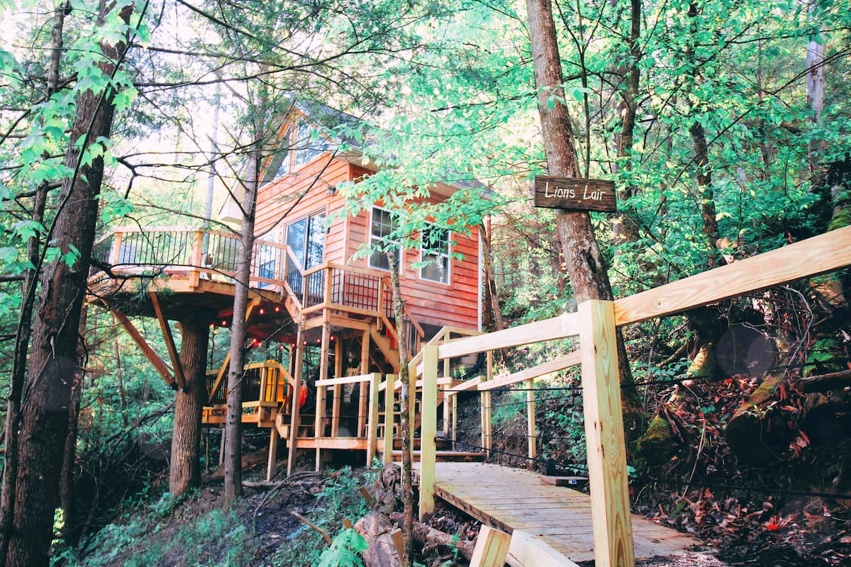 Photo treehouse cabin perched up on stilts in middle of forest