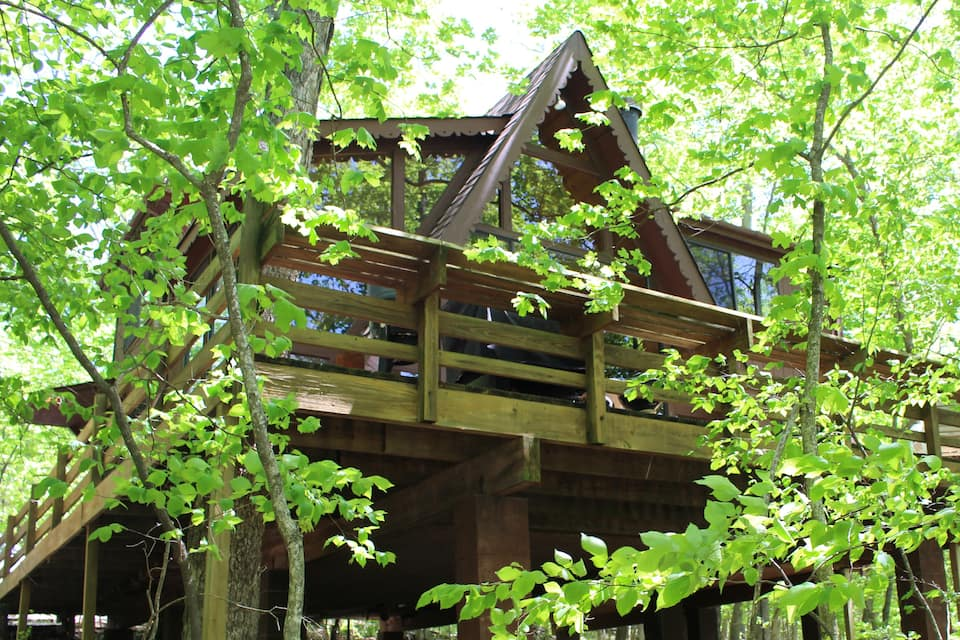 Photo of treehouse cabin on sunny day with lots of trees surrounding it.