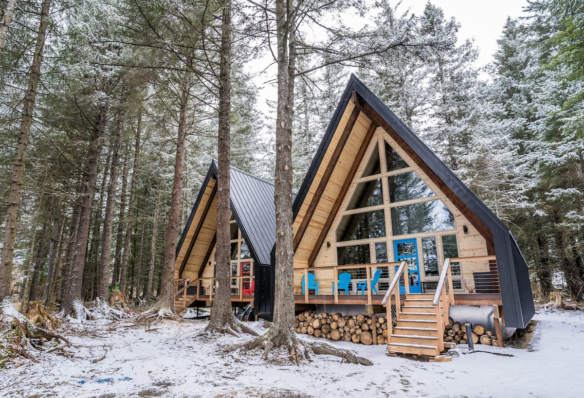 Lovely winter shot of an A-frame with large windows and blue chairs with lovely front porch.