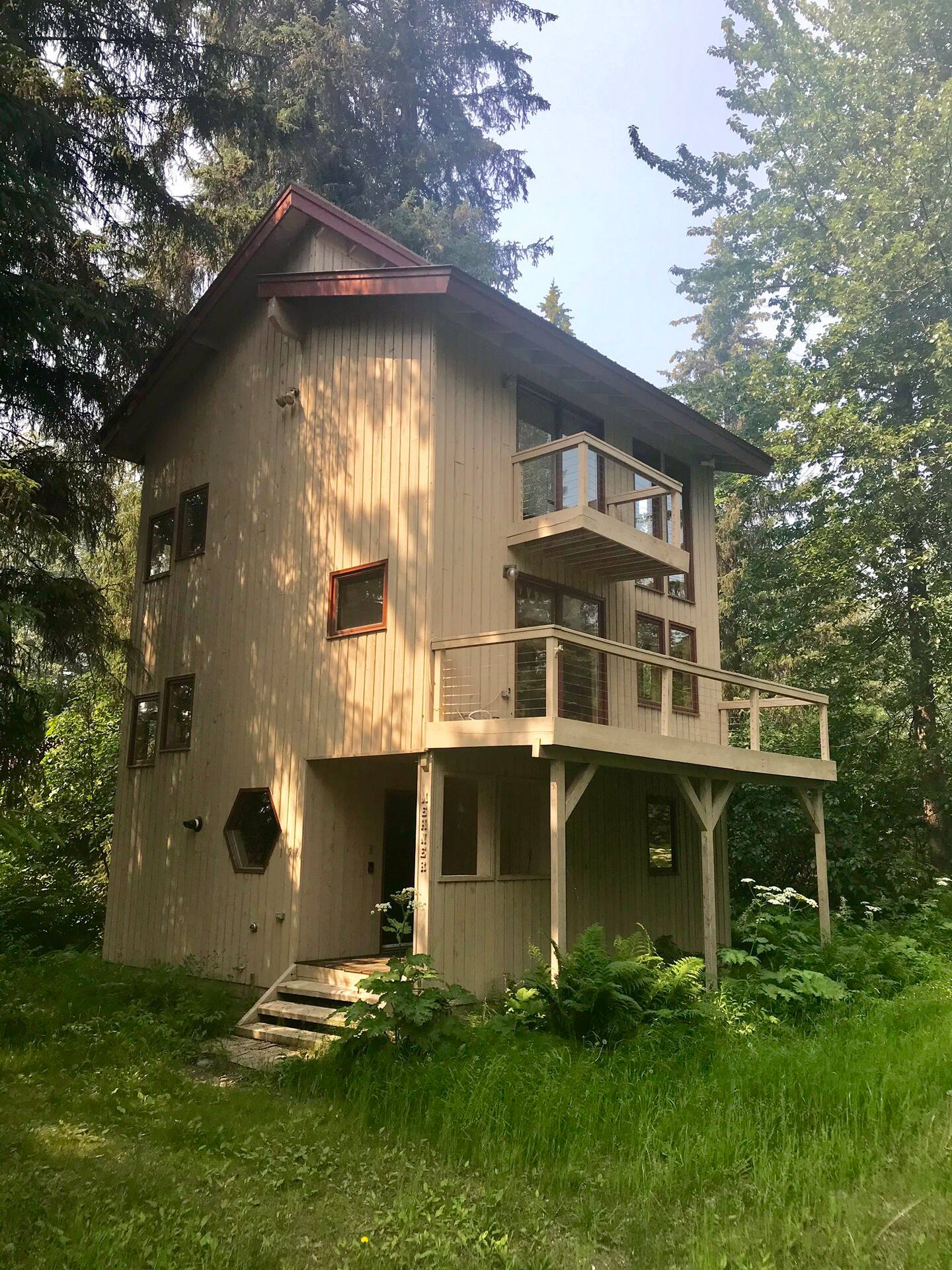 Large cabin painted beige with brown trim around every window, with balcony. One of the nicest Alaska rental cabins.