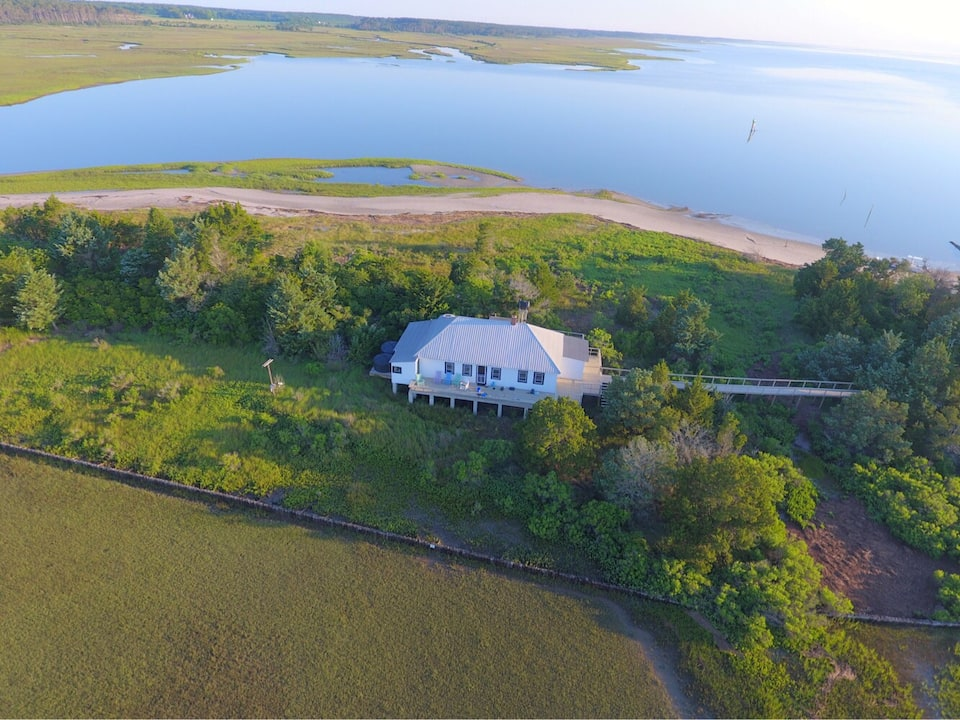 Overhead shot of white cabin on beautiful island surrounded by water with boardwalk leading off to the right