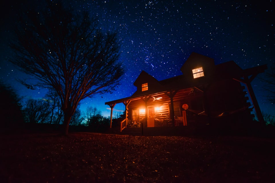 stunning photo of Virginia cabin at night with two front porch lights illuminated, against a bright starry sky.