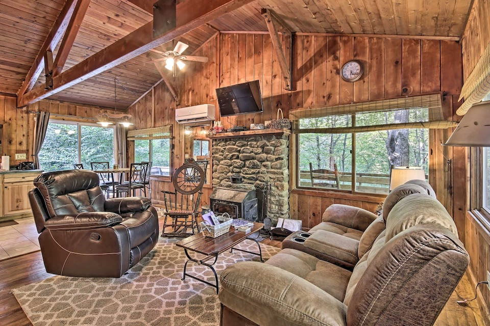 Luxury cabin rental in Virginia do not come much better than this one: high-quality wood throughout living room with over-sized recliners and large windows to see nature outside.