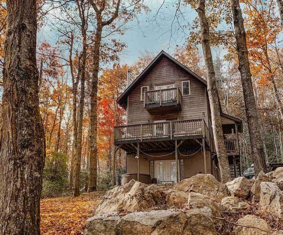 Beautiful multilevel brown wooden cabin surrounded with autumn leaves on trees with large rocks in foreground.