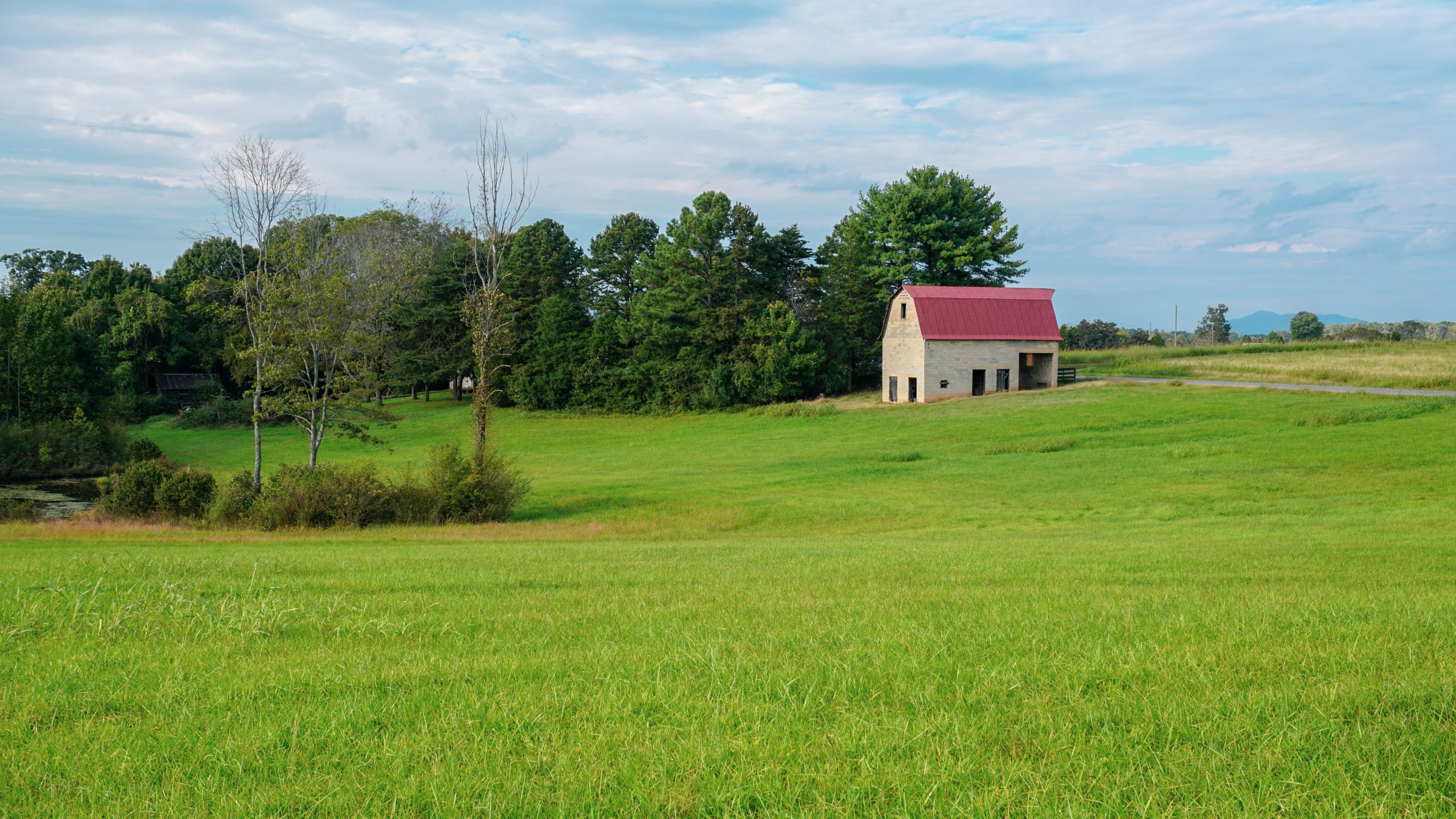 cute white barn with red roof in the Virginia countryside surrounded by lush green grass.