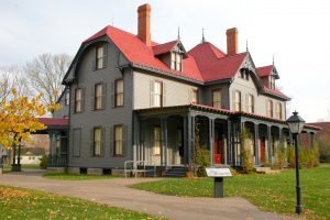 three story gray house with red roofing