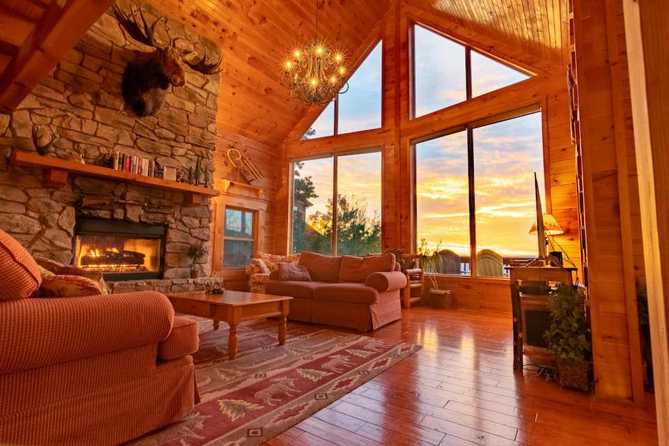 Living space inn log cabin with large windows showcasing sunset