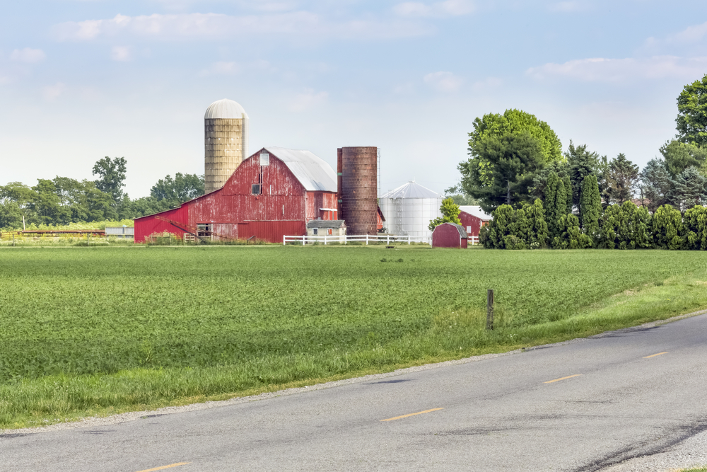 Red barn on large farm with green pasture in foreground signals one of the best towns in Ohio is close by.