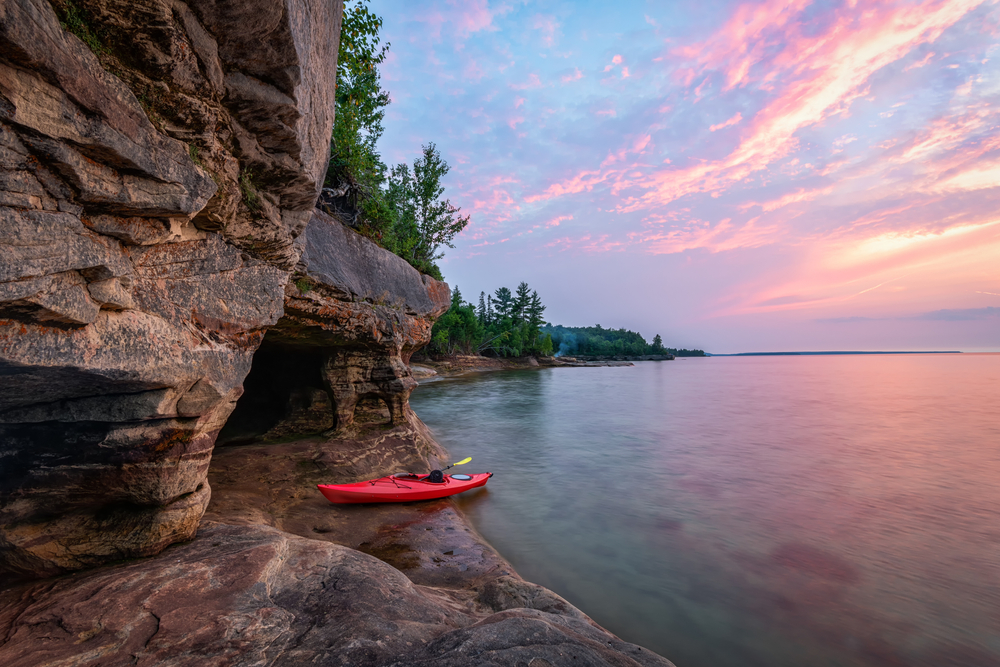 Sunset on Great Lake in northern Michigan with red kayak in center.
