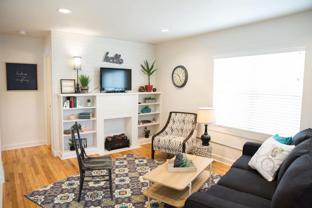 Charming living room with cozy chairs and blue couch in foreground. Attractive built-ins in background hold books and knicknacks.