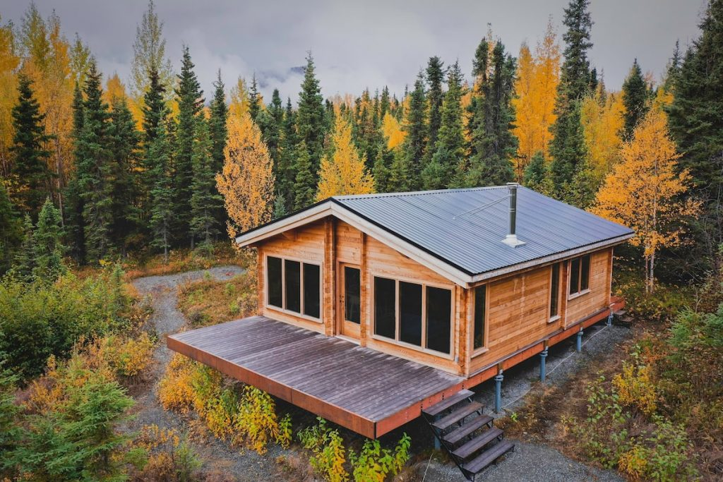 Beautiful Alaska cabin rental with lots of windows, green metal roof, large front deck and surrounded by autumn trees.