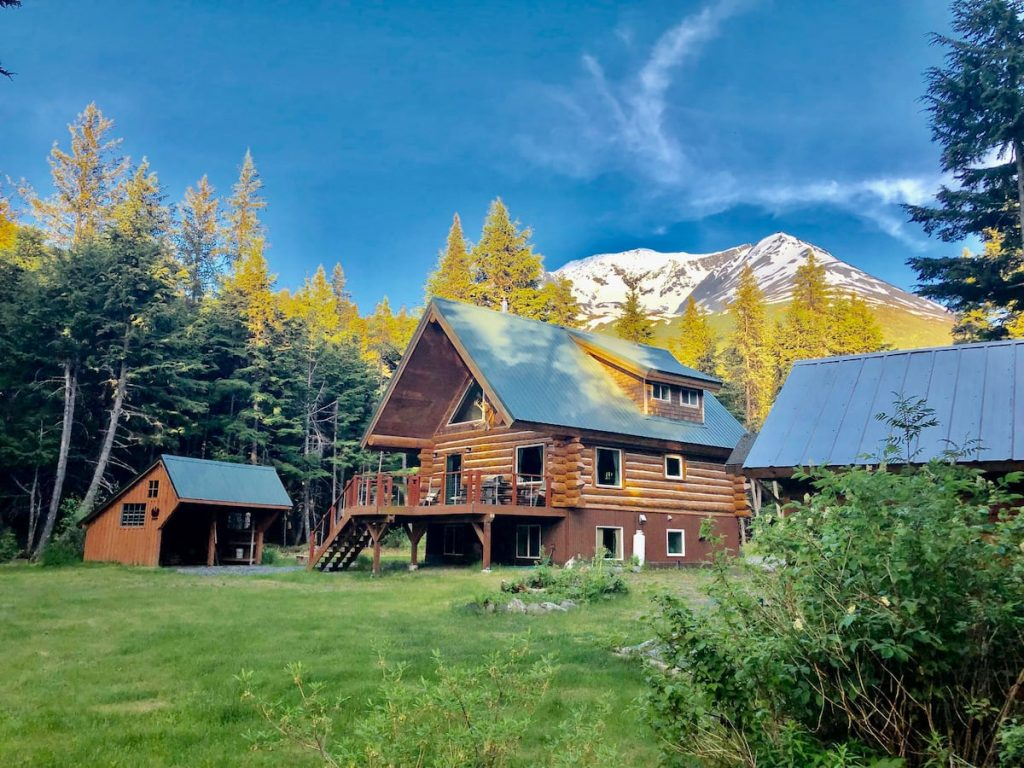 This is one of the best log cabins in Alaska and this photo shows it nestled in the snow-capped mountains. Cabin has green metal roof and large windows,