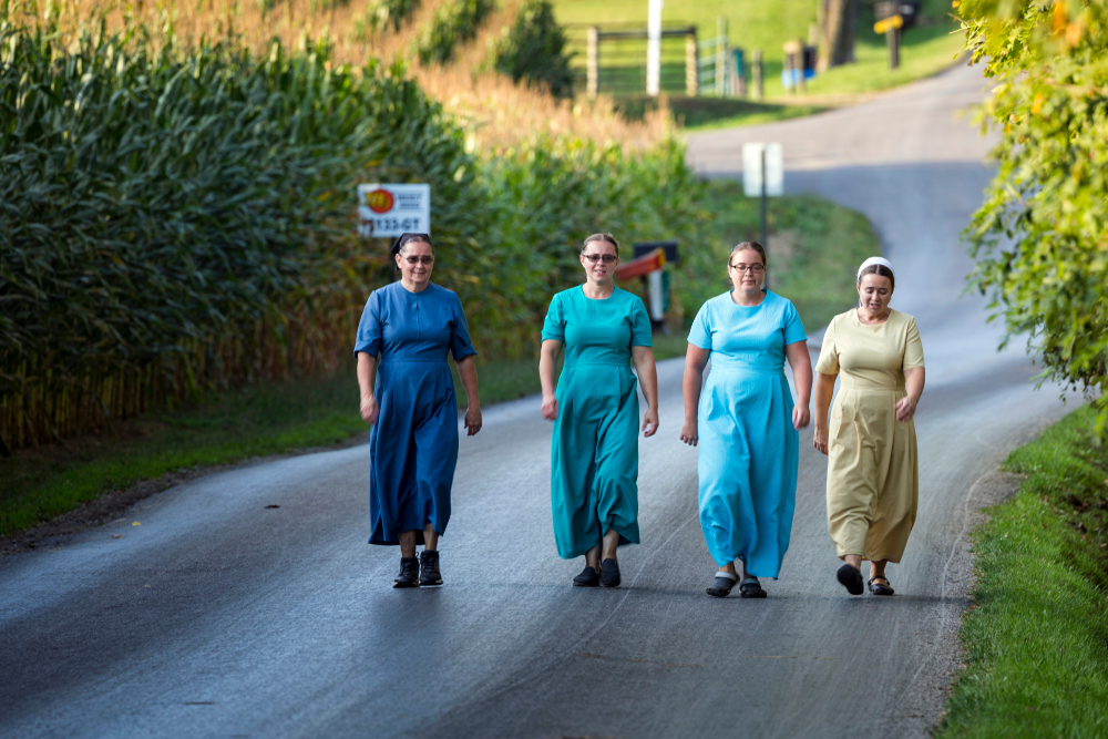 Four Amish woman walking up a road