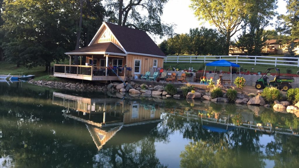 Cozy cabin on pond with large deck and colorful chairs along the pond