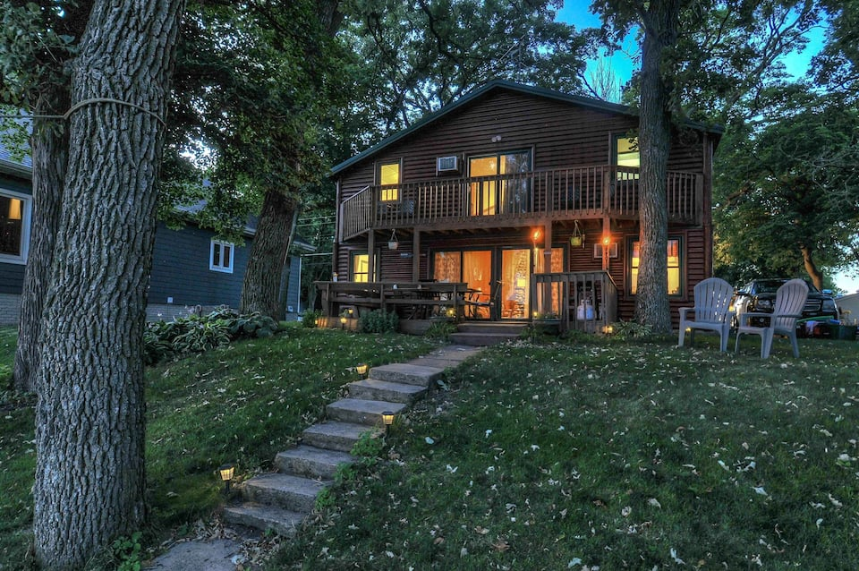 Photo of large 2 story cabin with warm lights from indoors lighting it. There are 2 chairs, and steps leading down through a green yard.
