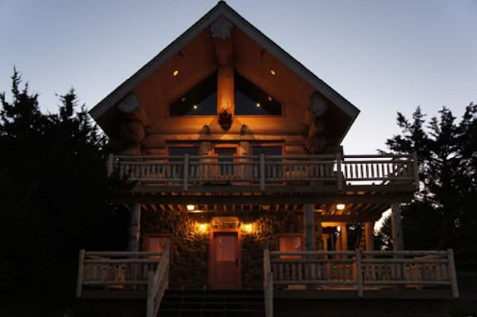 Twilight photo of beautiful cabin illuminated with soft white lights, with 2 balconies.