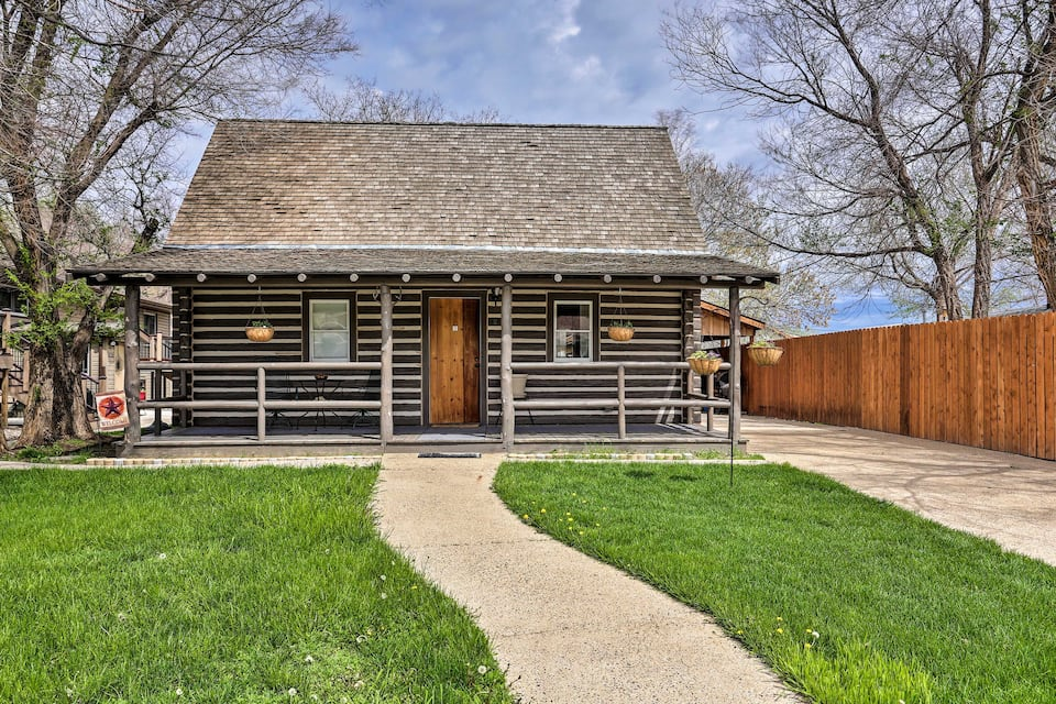 This rustic log cabin with brown siding and large front porch is one of the cool cabins in North Dakota.