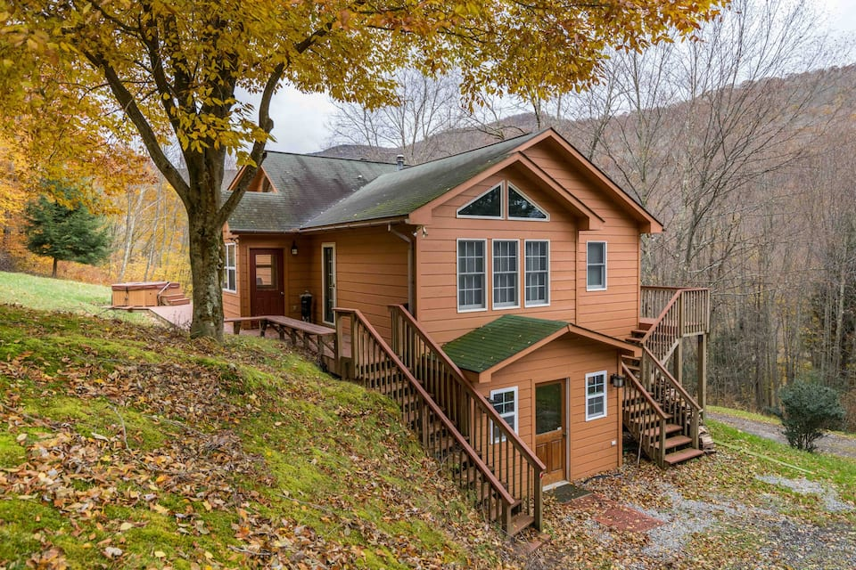Brown multi-level cabin with staircases on front and back of  it surrounded by trees.