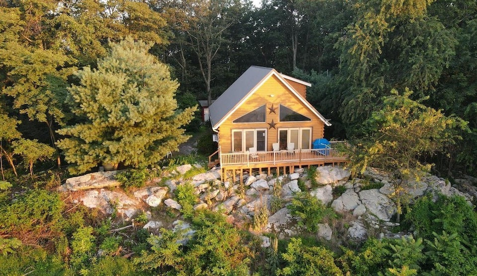 Drone photo of cabin in West Virginia with large windows, large front deck, surrounded by green forested trees.
