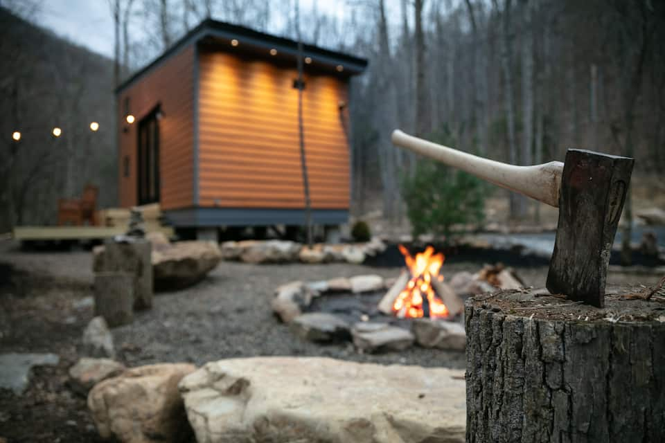 Photo of tiny cabin in West Virginia illuminated, with fire pit and hatchet in log in foreground.