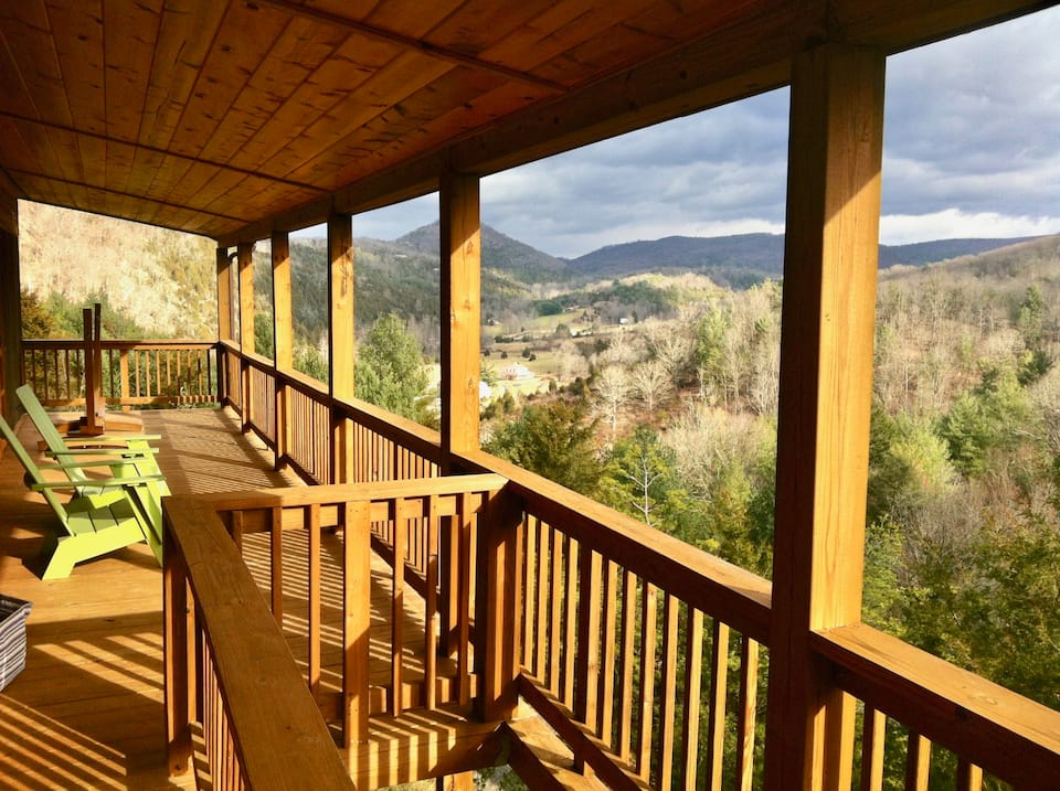 Photo of gorgeous wrap around balcony of cabin in West Virginia with views forever. Green Adirondack chairs on balcony.
