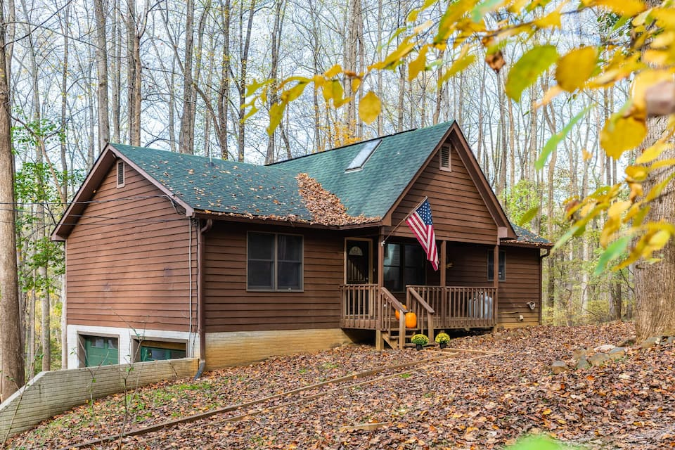 Brown cabin in West Virginia with green roof set amongst trees with screen-in front porch with American flag flying.